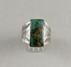 Lovely old green turquoise rectangle is set in a tooled silver ring, Navajo style.