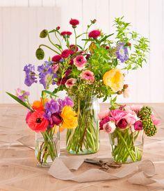 Ramos de flores de colores en amarillo, rojo, lila y rosa en jarrones de cristal