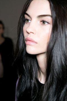 Dark brown / black hair with green hazel eyes and pale skin. Natural makeup, backstage, clean dewy skin, dark brows