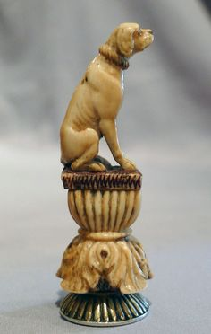 """Antique ivory and silver seal modelled as a seated hound sitting on an Acanthus flower base with reeded sides and reeded top to seal. Superbly carved dog, wearing collar, great detail and a lovely colour to the ivory after being handled for so many years. The seal has a lion standing with an arrow in its mouth to the centre and the latin inscription """"HAUD SECUS IN BONIS"""" around the outside. Probaly English and probably late 18th or early 19th century."""