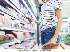 Young woman shopping healthy food in supermarket blur background. Close up view girl buy products using smartphone in store. Person comparing the price of produce. Hipster at grocery using smartphone.