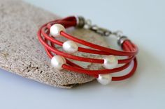 Leather and pearl bracelet, red leather cord with 5 freshwater pearls. Gift boxed. Silver plated rope pattern toggle clasp. Gift boxed.   This bracelet is 7.5 inches long, if you need it longer or shorter let me know in the notes to seller at checkout or contact me.  Please visit my shop to see other colors Ive made this bracelet in, or contact me if youd like a certain color. I have over 26 colors available!  This ships 2-3 days from your order via priority mail in the US, First Class…