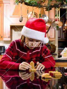 cute boy making gingerbread house. - Boy wearing santa hat and making gingerbread house while in the kitchen, Model: Josh Chapman