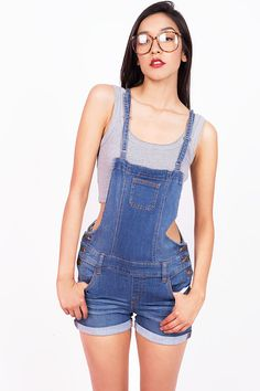 Denim shorts overalls with a cute fitted design and adjustable shoulder straps. Cuffed on the bottom with slight distressing and fade in the thighs. Pockets on the side and back with a trio of metal b