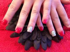 Acrylic nails with red polish and glitter ring ringer in glitter dust
