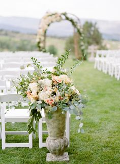 Tall urn with greens and flowers at the back of the ceremony chairs