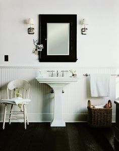 Light beadboard wainscoting with tall baseboard and a white wall above. Dark wood floor and mirror.