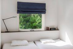 緑を絵のように切り取る窓のある寝室