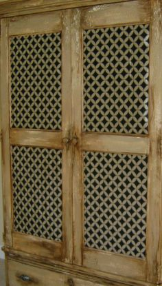 Distressed faux finish with fabric insets on armoire doors