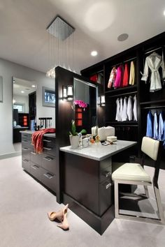 Plenty of closets have islands, but this one has a built-in dressing table as well – just the thing for coordinating wardrobe and makeup. This generously sized closet features high hanging clothes racks that smoothly descend down within reach via convenient pulls. Built by Visbeen Architects, Inc. for both her and him, this master closet is nestled between the master bedroom and master bathroom, its design reflecting the contemporary style of the rest of the home.