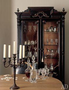В столовой — отреставрированный шкаф, доставшийся хозяйке вместе с особняком, посуда и подсвечник, Flamant.