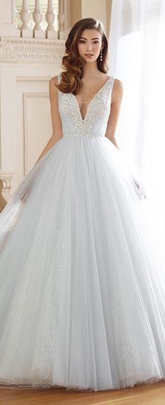 Sleeveless tulle and sequin tulle ball gown with hand-beaded shoulder straps, beaded deep V-neckline with lace appliqués and illusion modesty panel plunges down to beaded natural waist, deep V-back trimmed with beading, gathered full skirt with chapel length train.