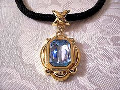 Blue Glass Pendant Necklace Gold Tone Vintage Avon Dramatic Brilliance Black Braided Cord - $39.00 USD Large clear blue square faceted glass stone raised layered decorative criss cross bale hook pendant choker necklace gold tone smooth metal finish vintage Avon Dramatic Brilliance collection. Measures 18 inch long black cord and link chain. Pendant measures 2 1/8 inches long, 1 inch wide. #holidaygifts http://PrettyJewelryThingsStore.com
