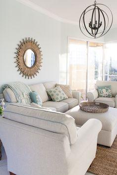 Florida house decor - beachy coastal decor with Top Sail by Sherwin Williams aqua paint. Cream couches, a striped ottoman and a sunburst mirror.
