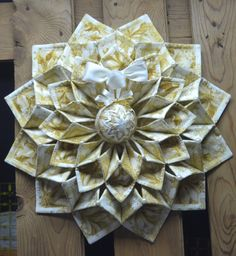 """40.00 USD 19"""" Christmas fold'n stitch wreath done in cream and gold matalic fabric accented with a quilted Christmas ball."""