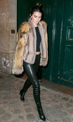 Kendall Jenner wears a faux fur coat, crop top, leather pants, and lace-up booties