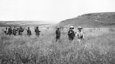 Circa 1890: A group on a big game hunting trip make their way across an African plain.