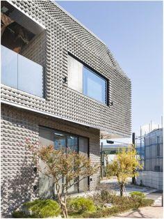 Uma casa com efeito texturizado no revestimento graças a tijolos angulares. O escritório sul coreano JOHO Architecture conseguiu essa fachada super diferente brincando com os ângulos dos tijolos cinzas. O efeito é tanto visual quanto sensorial.