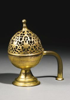 AN OTTOMAN TOMBAK INCENSE BURNER, TURKEY, 17TH/18TH CENTURY of baluster form, the ovoid body supported on a stepped splayed foot with a domed hinged openwork cover designed with palmette motifs and a faceted handle  20.5cm. height.