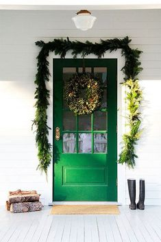 Festive welcome with a bright green door decorated with garland and a wreath