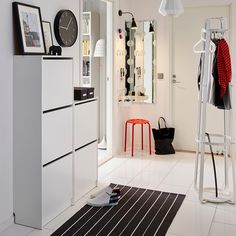 Ikea Bissa Shoe cabinets - I like the use of two at different heights and the arrangement of art/clock above it. Ikea Hallway, Ikea Entryway, White Hallway, Entryway Shoe Storage, Hallway Furniture, Hallway Decorating, Interior Decorating, Ikea Shoe Cabinet, Shoe Cabinets