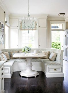 pretty colors, nice pedestal table and banquette millwork...dark stained floors with pastel colors
