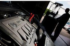 Ein Kfz-Meister lädt im Rahmen einer Rückrufaktion zum Abgasskandal ein Software-Update auf einen VW-Auto. Foto: dpa