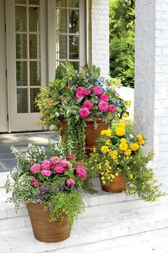 "These porch-step containers begin with bright pink and yellow zinnias. Cooler ""filler"" flowers, such as purple verbenas and blue calibrachoas are added to create contrast with texture and color. Opt for inexpensive plastic planters that are weatherproof and easy to move around. Grouping them in a tight space creates a homey, mini-garden vibe. Plus, when placed side by side, all of the colors intensify."