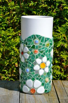 Tall ceramic vase covered in glass and ceramic tile mosaic. Includes ceramic pieces, glass tiles, glass beads and glass drops, mother of pearl, dichroic glass drops and millefiori. Grouted in pale green. Made from a recycled vase, still perfect on the outside, but some signs of wear on the inside. Measures 11 (27 cm) tall and 4,5 (11 cm) in diameter.