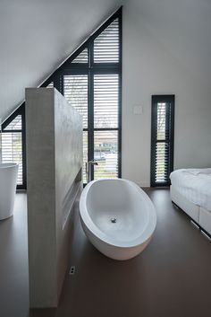 Beautiful open bathroom in the bedroom. The roomdivider is finished with Top Ciment Mircodeck. Made by StucArt. The beautiful Elaine bath by JEE-O. And tough black shutters by Jasno. Tight cast floor made by B-Art Works. Een prachtige open badkamer in de slaapkamer. De roomdivider is afgewerkt met Top Ciment Microdeck. Aangebracht door StucArt. Prachig vrijstaand Elaine bad van JEE-O. En stoere zwarte shutters van Jasno. Strakke gietvloer aangebracht door B-Art Works.