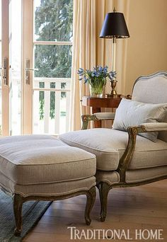 Warm taupe upholstery on the French Country Chair and Ottoman invites a sit. - Traditional Home ® / Photo: John Granen / Design: Mary Silk