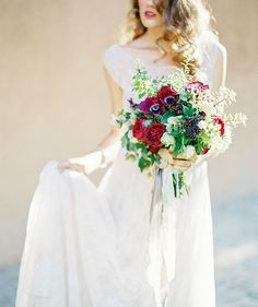 The deep, rich reds of this bouquet and the soft drape of her beaded lace gown are like a dream