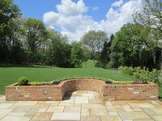 Garden with Curved Reclaimed Brick Planters, Indian Sandstone Paving and Lawn