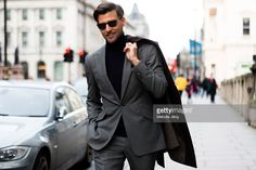 Model Johannes Huebl attends the Pringle of Scotland show in a gray Marc Anthony tailoring suit and coat, black Brunello Cucinelli turtleneck, and brown Russell & Bromley oxfords during The London Collections Men AW16 on January 10, 2016 in London, England.