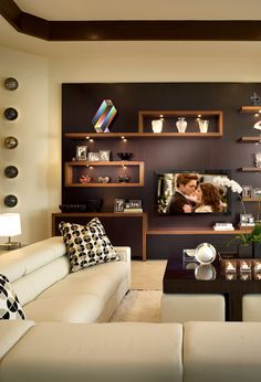 Nice floating shelves instead of a wall unit, can mount tv in the middle.  Comfy looking modern sofa, area rug, and dark coffee table.