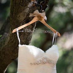 We just adore when wedding photographers hang the brides dress in natural scenery. #weddinghangers #smpweddings #etsy #bridalhanger #theknot #RusticWedding #southernbrides #southernweddings