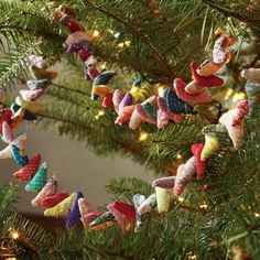 """SARIS REBORN GARLAND--Dozens of plump pillows cut from vintage cotton saris create a garland of color and pattern to trim your tree, mantel or buffet table. Button loop closure. Each garland is unique. Imported. Exclusive. 70""""L."""