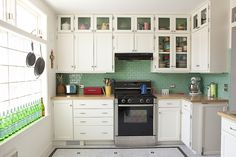 white cupboards, turquoise subway tile, b&w hex floor tile, glass front cupboards at top