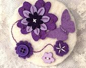 Purple and white felt brooch with embroidery and embellishment