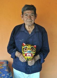 "Mask maker Jose ""Che"" Luna holds one of his creations — a wooden tiger mask. Mexican Mask, Mexican Folk Art, Central America, South America, Collages, Tiger Mask, Mexico Travel, First Nations, Portrait"