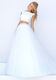 Stretch crop top two-piece prom dress delicately iced with matching Swarovski crystals. a-line skirt is soft tulle. Bateau neck, cap sleeves. Colors: White.