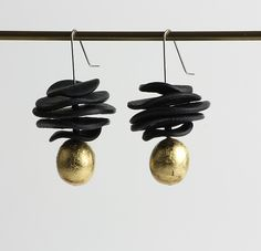 Created by Klara Borbas  Five black polymer discs and a gold leaf covered polymer bead on stainless steel wire. $90.00