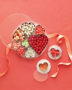 Heart shaped cookie cutters filled with candy placed inside of round containers.  Shown as favors but could also be put around the house for a party, put on tables at a wedding or bridal shower, etc.