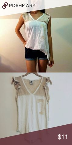 (NWT) #7 Tan Tee With ruffled edges, this cute tee is great to wear on a casual day out and easily pairs with jeans or shorts. It has a high-low design to it and a matching tan #7 on the shirt! Rebel Yell Tops