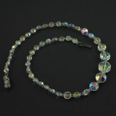 Graduated aurora borealis necklace. Set with a rhinestone push in clasp. Circa 1950`s.  Size : 43cm ( 17″ ) long, graduated from 14mm – 6mm, weight : 22g.  Period : Mid-Century Jewellery ( 1950s ).  All items are presented in one of our beautiful signature boxes. Free worldwide delivery on all purchases.