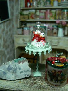 Snowman under glass cloche on cake pedestal. Dollhouse Christmas decor. Miniature.