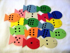 make fish with dots out of foam sheets, attach paper clip on the tip, place fish n a small pool or bathtub (or just spread onto the ground), choose card that has a number on it and use a magnetic fishing pole to fish out the correct matching fish.