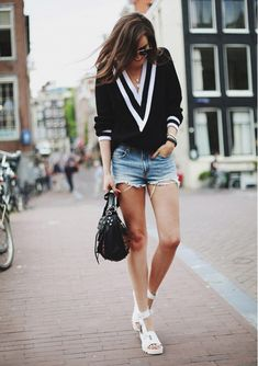 Andy Torres of Style Scrapbook in a black and white V-neck sweater, denim cutoffs, and white platform sandals