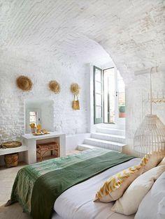 Chambre immaculée et son toit voûté, plaid vert et coussins dorés