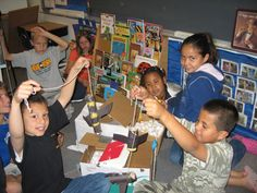 Photo shows seven youngsters around a table with paper, string and construction paper.